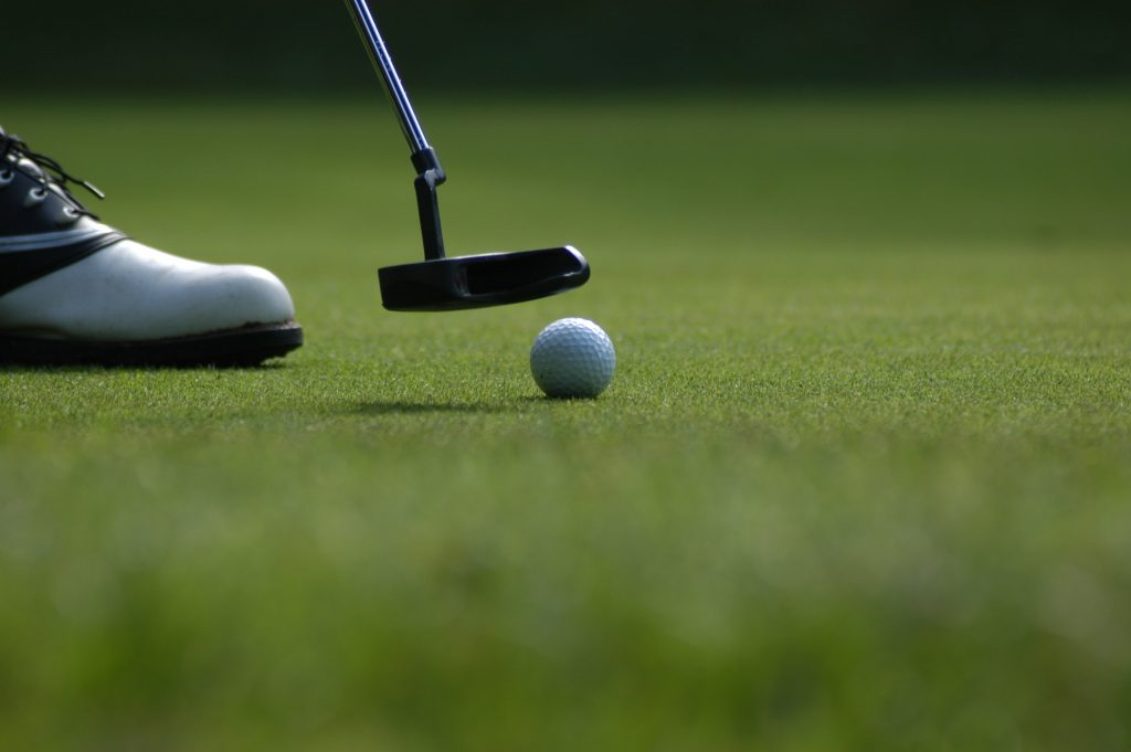 Photo of golfer putting, close-up of ball